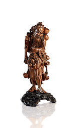A CARVED WOOD FIGURE OF AN IMMORTAL WITH PEACHES OF LONGEVITY
