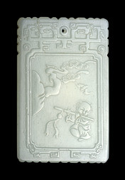 A PALE JADE PENDANT WITH A BOY PLAYING A FLUTE