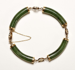 A GREEN JADEITE AND SILVER BRACELET