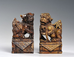 A PAIR OF CARVED SOAPSTONE FIGURES OF SEATED CHINESE LIONS