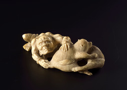AN IVORY OKIMONO OF AN ONI WITH TWO TANUKI