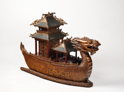A CARVED RED LACQUERED AND GILT DECORATED WOODEN MODEL OF A DRAGON BOAT