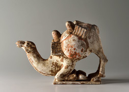 A PAINTED POTTERY FIGURE OF A KNEELING CAMEL