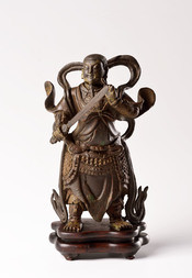 A CAST IRON FIGURE OF A STANDING GUARDIAN
