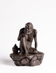 A CAST IRON FIGURE OF A SEATED LUOHAN