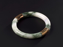 A WHITE AND DARK-GREEN JADEITE BANGLE