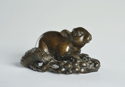 A BRONZE OKIMONO OF A SQUIRREL AND GRAPES