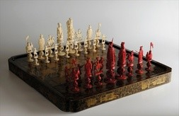 A FINE IVORY CHESS SET WITH LACQUERED CHESS-BOARD