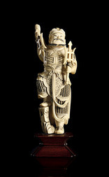 AN IVORY FIGURE OF A STANDING GUARDIAN