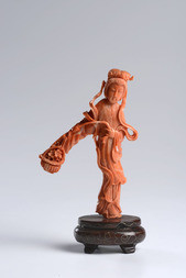 A CARVED CORAL FIGURE OF HE WITH A FLOWER BASKET