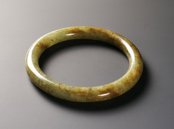 A MOTTLED GREEN AND BROWN JADE BANGLE