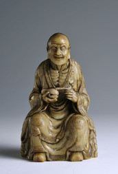 A SOAPSTONE FIGURE OF A SEATED LUOHAN