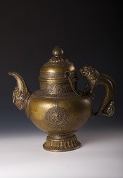 A LARGE BRASS TEA POT DECORATED WITH SILVER