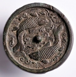 A BRONZE MIRROR WITH FISH IN RELIEF