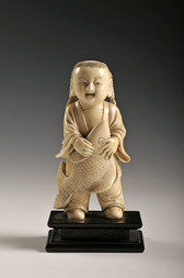 A CARVED IVORY FIGURE OF A SERVANT BOY WITH A CARP