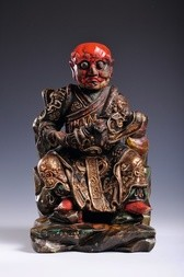 A CARVED, GILDED AND POLYCHROME WOOD FIGURE OF SEATED GUANDI
