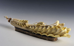 AN IVORY CARVING OF A GRASSHOPPER ON A CABBAGE LEAF