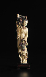 A CARVED IVORY FIGURE OF A BEAUTY WITH PEONIES