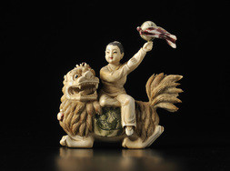 A CARVED IVORY FIGURE OF A GIRL WITH A BALL ASTRIDE A LION