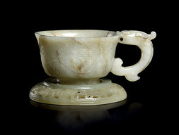 A PALE AND DARK BROWN JADE CUP WITH DRAGON HANDLE AND PIERCED SAUCER