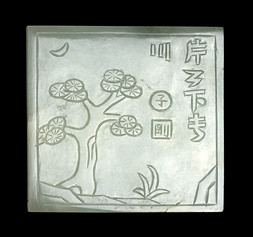 A SQUARE CELADON JADE PLAQUE CARVED WITH A PINE TREE