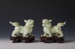 A PAIR OF JADEITE LIONS ON HARDWOOD STANDS