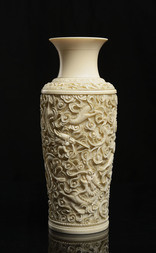 A CARVED IVORY VASE WITH DRAGONS