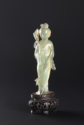 A PALE GREEN JADEITE FIGURE OF HE XIANGU